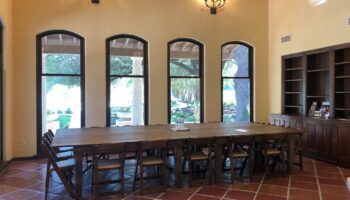 Meeting Room at Garey House, set for a corporate meeting at farm tables, with view of built-in bookshelves