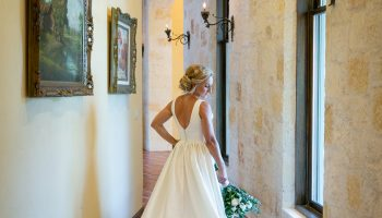 Bride posed with bouquet by paintings in the hallway to the left side of the venue, by Addison Studios