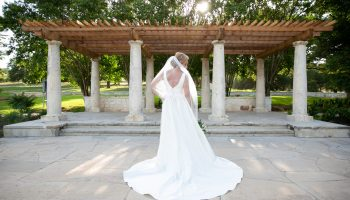 Bride posed in front of the pergola at the Terrace, with her back facing the camera, and flowing veil and dress train behind her