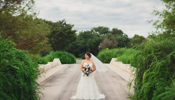 Bride posed with bouquet on the stone bridge at Garey House, between lush green bushes