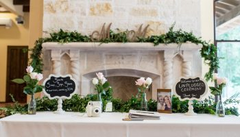 Guest book and sign in table set in front of the Great Room fireplace, with garland runners on the mantle and table