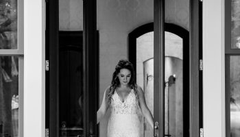 Bride exiting out of the double doors from the Office/Trophy Room (black & white)