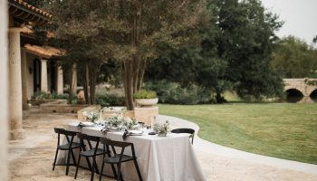 Dining table on the back patio of Garey House, with grey linen, black modern chairs and table settings for 6