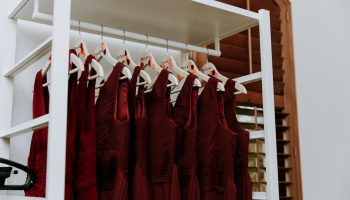 Close-up of burgundy dresses hanging on a white dress rack in the large prep suite