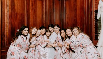 Bride and nine bridesmaids hugging in front of wood wall in the large prep suite