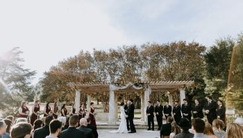 Wedding party up the steps of the Terrace, with guests seated in front of them, with fabric wrapped pillars and fall leaf crepe myrtles behind
