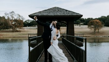 Bride and groom kissing on the dock over the pond, with groom's fist pumped up into the air
