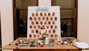 Donut wall, 3-tiered cake, greenery and scattered florals set-up on a farm table