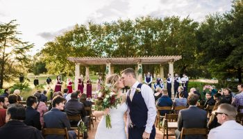 Bride and Groom kissing at the end of the ceremony aisle at the Terrace after being pronounced Mr. and Mrs.
