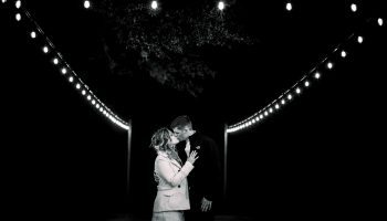 Bride and groom kissing under the festoon lights at the Courtyard at night