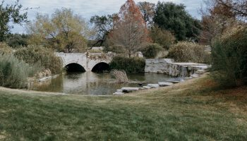 The waterfall spillover pond and double-arched stone bridge with Fall colored trees behind