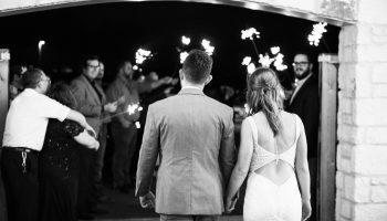 Bride and Groom walking through the Courtyard gates for a sparkler send-off (black and white)