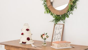 Farm table set-up with bride and groom's cake, against a white wall, with a round mirror framed with greenery