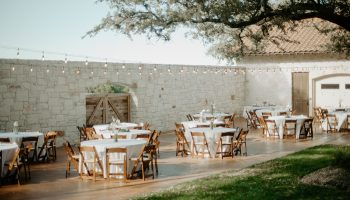 Reception tables with white linens set-up on the Courtyard, beneath the festoon lights