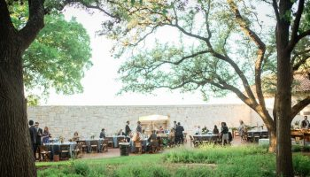 Reception tables set-up on the Courtyard from a far, peeking through 2 trees, with blue linens