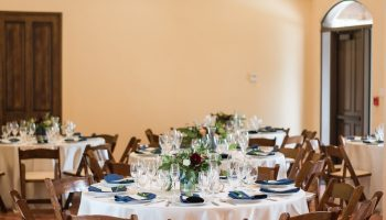 A far shot of 5 reception tables in the Great Room, with formal table settings, pops of navy napkins and floral centerpieces