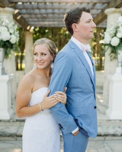 Annaliese + Sean - Posed front to back in front of the Terrace, with white floral arrangements faintly in the background