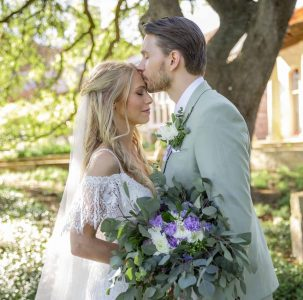 Antonia + Dylan - Groom kissing bride on forehead while holding green and purple bouquet