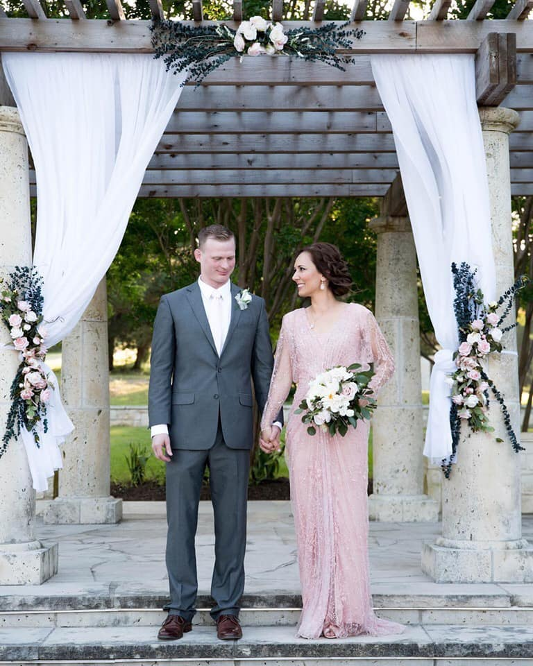 The Ellis' - Beneath the Terrace with pillars draped in fabric and floral accents
