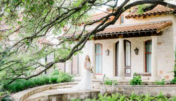 iew through the trees of a bride posed on the back porch of the large prep suite at Garey House