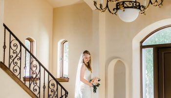 Bride posed on the stone stairs inside the entry way of Garey House with chandelier above
