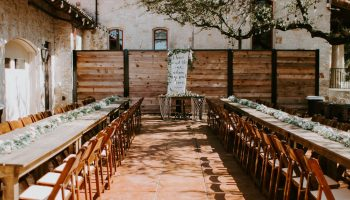 Family style dinner with seating at long farm tables, with sweetheart table in the middle at the Courtyard