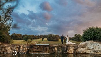 Bride and Groom walking on the waterfall ledge at sunset at Garey House