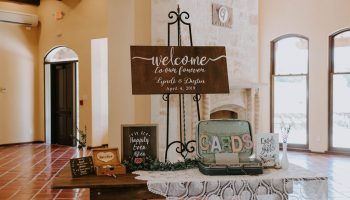 Welcome table on a wooden farm table in the Great Room with card box and accents