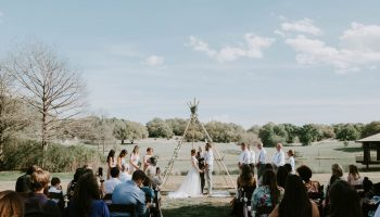 Boho wedding ceremony on the event lawn at Garey House, with guests facing a teepee style altar with pond behind
