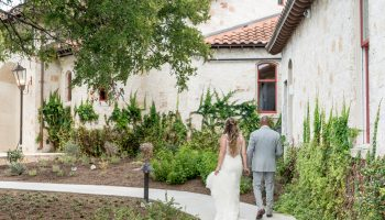 Bride and Groom walking along the sidewalk at the front of Garey House, next to the ivy covered wall