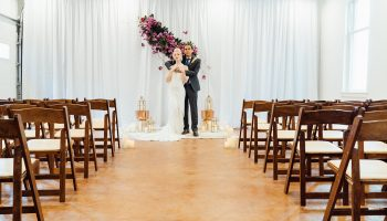 Bride and Groom posed in front of a ceremony set-up in the Hall, with white fabric backdrop and suspended purple flower arrangement, with ceremony chairs along the side