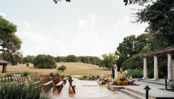 A side view of Bride and Groom standing on the Terrace steps with boho ceremony decor surrounding them and ceremony chairs to the left