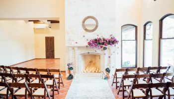 Wide shot of an indoor ceremony in the Great Room with a purple floral arrangement on the fireplace mantle, rug and copper pedestals on the ground, and candles glowing in the fireplace