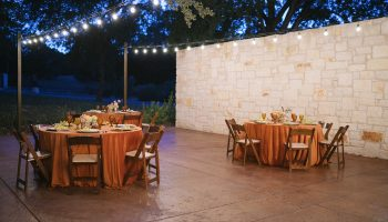 3 round reception tables with rust linens under string lights at the Courtyard