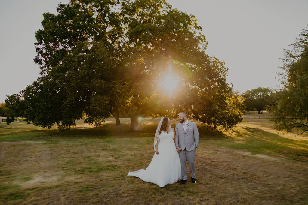 Catherine + Aaron in front of a large pecan tree at sunset on the Garey House grounds