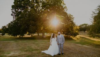 Bride and Groom in front of a large pecan tree at sunset on the Garey House grounds