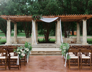 WEDDINGS - Ceremony at the Terrace with white fabric draped on the pergola, floral arrangement on the left, and greenery and white rose aisle markers on the chairs