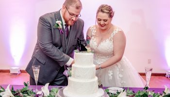 Bride and Groom cutting 3-tier cake in the Hall with purple up-lighting behind them