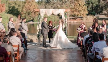 Fall wedding ceremony on the Terrace with the pond behind and wooden arbor decorate with fabric and greenery