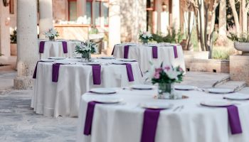 4 Reception tables set on the back patio with white china and purple napkins