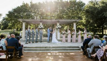 Wedding party standing on the middle level of the Terrace during a wedding ceremony, with guests seated in front on the lower level, and sunset peeking through the top of the trees