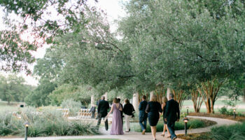 Wedding guests walking along the sidewalk beneath the oak trees, to a ceremony at the Terrace