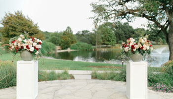 2 large floral arrangements in round pots, set on white pedestals, with view of the pond behind