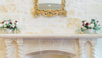 Stone fireplace with twisted mantle legs, with gold mirror hung above and a floral arrangement on each edge of the mantle