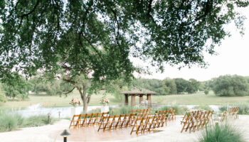 An angled view of a ceremony on the Terrace from the sidewalk, with floral arrangements on 2 white pedestals and fruitwood folding chairs facing the pond