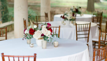 3 reception tables with white linens, fruitwood chivari chairs and floral centerpieces, set on the Meeting Room porch