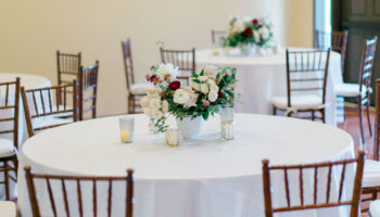 Reception tables with white linens, fruitwood chivari chairs and floral centerpieces, set in the far Great Room