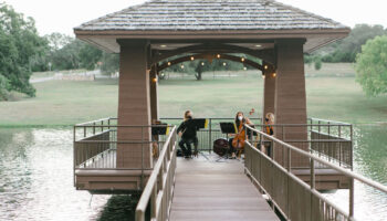 String quartet seated with instruments on the dock over the pond, playing for the wedding ceremony