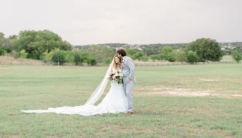A couple posted in the grass with groom kissing the bride's head, dress train and veil off to the left, and view of the Meadow behind them