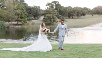 Bride and Groom holding hands, walking in front of the pond and fountain, dress train trailing behind and trees in the background